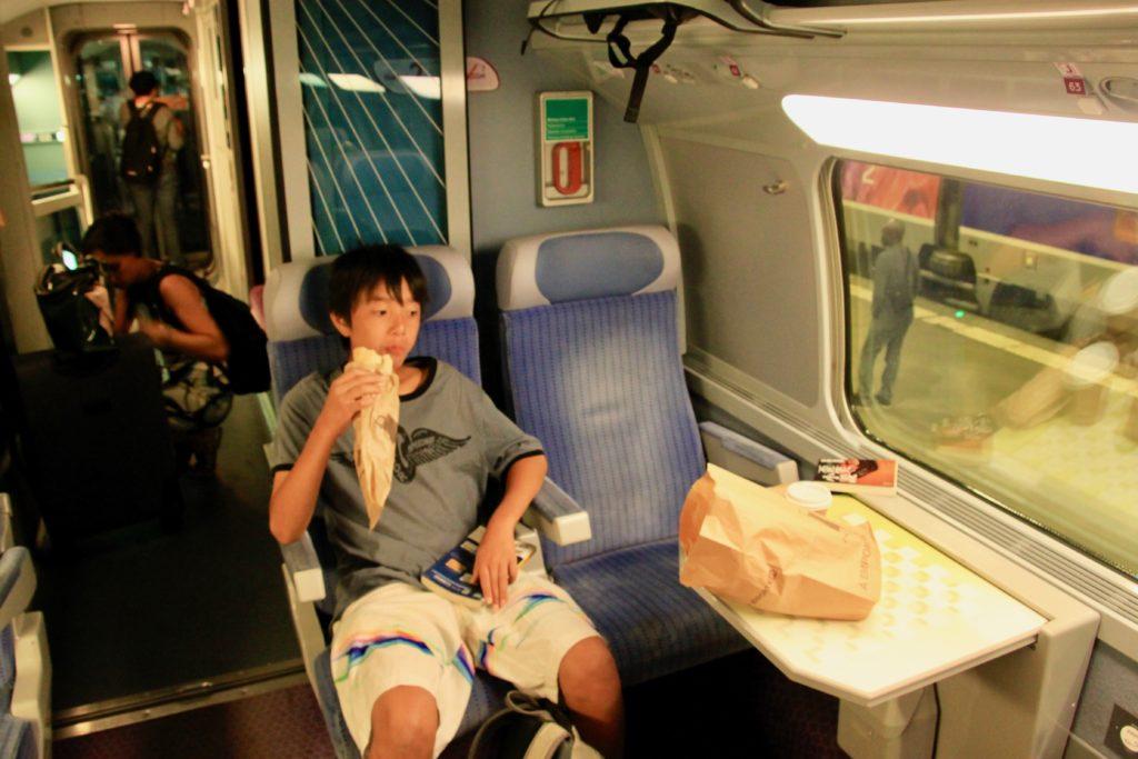 シートに座って駅で買った朝食のサンドイッチを食べる次男