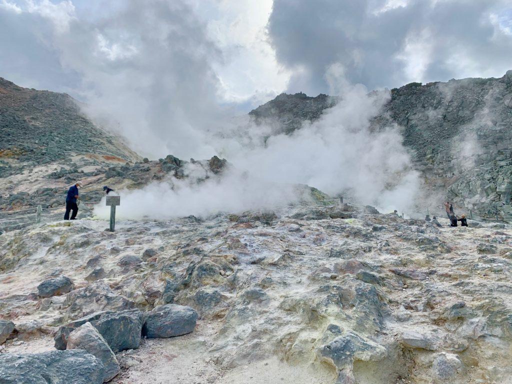 噴煙が上がる硫黄山の噴火口