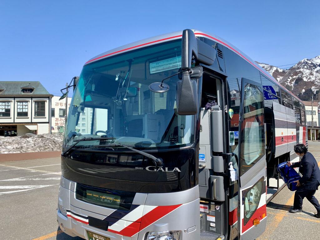 送迎バスに荷物を積み込むスタッフ
